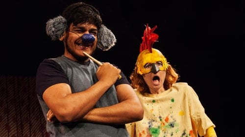 A production shot from the family show Something Else. A creature with a blue nose looks happy. sanding next to him a woman with a chicken mask looks shocked.